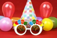 Glückliche Geburtstagsfeiergläser, Parteihut und Parteiballone auf rotem Hintergrund Stockbild