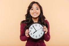 Glückliche Gefühle der asiatischen Frau mit dem gelockten langen Haar, das Uhr hält Stockfotos