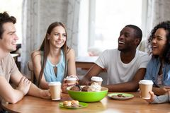 Glückliche gemischtrassige Freunde, die zusammen Freizeit im Café verbringen lizenzfreie stockfotografie