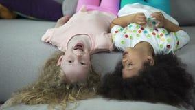 Glückliche gemischtrassige Kinder, die auf Couch liegen und Spaß, Kindheit und Feiertage haben stock video footage