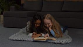 Glückliche gemischtrassige Kinder, die zu Hause Märchen lesen stock footage