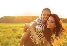 Glückliche genießende liebevolle Mutter, die ihren spielerischen lachenden Kindgi umarmt Lizenzfreies Stockfoto