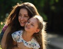 Glückliche genießende Mutter, die ihr Entspannungslächelndes Kindermädchen auf b umarmt Stockfotografie