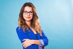 Glückliche Geschäftsfrau in den Brillen, welche die Kamera über blauem Hintergrund betrachten Stockbild