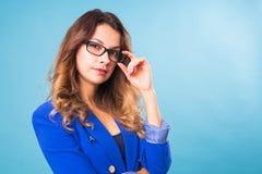 Glückliche Geschäftsfrau in den Brillen, welche die Kamera über blauem Hintergrund betrachten Lizenzfreies Stockfoto