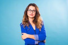 Glückliche Geschäftsfrau in den Brillen, welche die Kamera über blauem Hintergrund betrachten Lizenzfreie Stockbilder