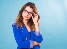 Glückliche Geschäftsfrau in den Brillen, welche die Kamera über blauem Hintergrund betrachten Lizenzfreie Stockfotografie