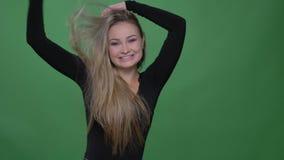 Glückliche Geschäftsfrau in der schwarzen Bluse, die herum spinnt und Unterhaltung in Kamera am grünen Hintergrund zeigt stock footage