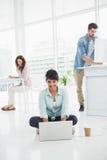 Glückliche Geschäftsfrau, die auf dem Boden unter Verwendung des Laptops sitzt Stockfotos