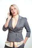 Glückliche Geschäftsfrau, die auf dem Smartphone lokalisiert auf weißem Hintergrund spricht Lizenzfreies Stockfoto