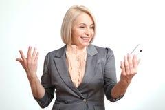 Glückliche Geschäftsfrau, die auf dem Smartphone lokalisiert auf weißem Hintergrund spricht Lizenzfreie Stockfotografie