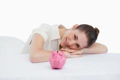 Glückliche Geschäftsfrau, die auf ihrem Schreibtisch mit einer piggy Bank sich lehnt Stockfotografie