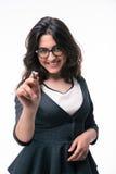 Glückliche Geschäftsfrau, die auf Kamera mit Stift zeigt Stockfoto