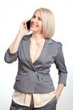 Glückliche Geschäftsfrau, die auf Smartphone auf weißem Hintergrund spricht Lizenzfreie Stockbilder