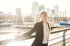 Glückliche Geschäftsfrau, die draußen nahe dem Fluss lacht Stockbilder