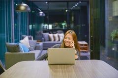 Glückliche Geschäftsfrau, die einen Laptop im Wohnzimmer nachts verwendet stockfoto