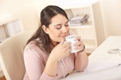 Glückliche Geschäftsfrau, die Kaffeepause im Büro hat Lizenzfreie Stockbilder