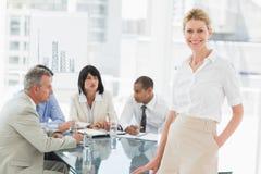 Glückliche Geschäftsfrau, die Kamera betrachtet, während Personal hinter ihr sich bespricht Lizenzfreies Stockbild