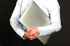 Glückliche Geschäftsfrau, die mit dem Laptop lokalisiert auf einem schwarzen Hintergrund steht lizenzfreies stockbild