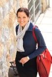 Glückliche Geschäftsfrau, die nach Hause reisendes Gepäck ermüdet ankommt Stockfoto