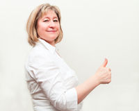 Glückliche Geschäftsfrau, die sich des Daumens zeigt Stockbilder