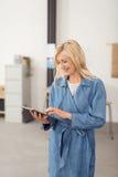 Glückliche Geschäftsfrau, die unter Verwendung einer Tablette steht Lizenzfreies Stockfoto