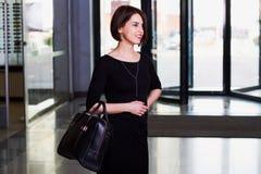 Glückliche Geschäftsfrau im schwarzen Kleid gehend mit Aktenkoffer in SH Lizenzfreie Stockbilder