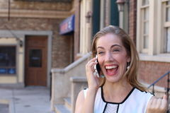 Glückliche Geschäftsfrau mit dem Mobiltelefon, das gute Nachrichten auf der Straße erhält Lizenzfreies Stockfoto