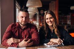 Glückliche Geschäftsfrau und ihr Kollege, die Kamera beim Arbeiten im Café betrachtet Lizenzfreie Stockfotografie