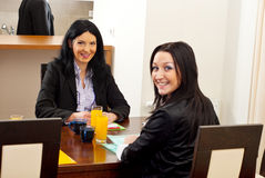 Glückliche Geschäftsfrauen am Versammlungstisch lizenzfreies stockfoto