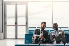 glückliche Geschäftskollegen, die auf Flug im Flughafen warten Lizenzfreie Stockfotografie