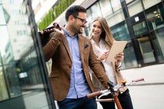 Glückliche Geschäftskollegen, die in die Stadt im Freien sprechen und gehen lizenzfreie stockbilder