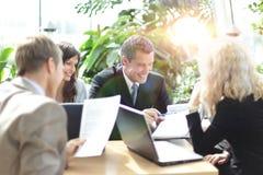 Glückliche Geschäftskollegen im modernen Büro unter Verwendung der Tablette Stockfotografie