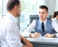 Glückliche Geschäftsleute, die auf Sitzung sprechen Stockfotos
