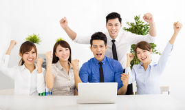 Glückliche Geschäftsleute, die bei der Sitzung zusammenarbeiten Stockbild