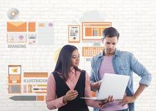 Glückliche Geschäftsleute, die einen Computer gegen weiße Wand mit Grafiken verwenden Lizenzfreie Stockfotografie