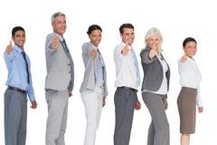 Glückliche Geschäftsleute, die Kamera mit den Daumen oben betrachten Lizenzfreies Stockfoto