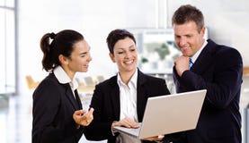 Glückliche Geschäftsleute mit Laptop Stockbild