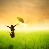 Glückliche Geschäftsregenschirmfrau, die auf dem grünem Reisgebiet und -sonnenuntergang springt Stockfotos