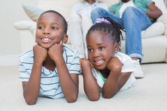 Glückliche Geschwister, die auf dem Boden liegen Stockfotos
