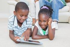 Glückliche Geschwister, die auf dem Boden unter Verwendung der Tablette liegen Stockfoto