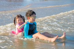 Glückliche Geschwister, die auf dem Strand spielen stockfoto