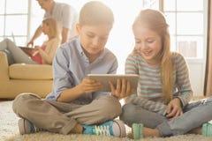 Glückliche Geschwister, die digitale Tablette auf Boden mit Eltern im Hintergrund verwenden Lizenzfreies Stockbild