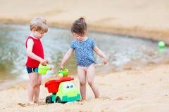 Glückliche Geschwister: Junge und Mädchen, die zusammen im Sommer spielen Stockfoto