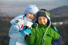 Glückliche Geschwister mit Schnee Stockfotos