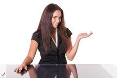 Glückliche Gesten junger Dame, gesessen am Schreibtisch, auf Weiß Lizenzfreie Stockfotografie