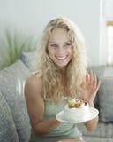 Glückliche gestikulierende Frau beim Halten des Kuchens im Haus Stockfotografie