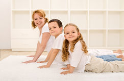 Glückliche gesunde Familie, die Gymnastikübungen bildet Lizenzfreies Stockbild