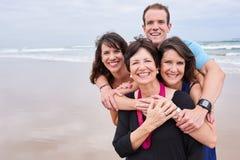 Glückliche gesunde Familie, die zusammen auf dem Strand umarmt und lächelt Stockbilder