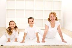 Glückliche gesunde Kinder und Frau, die Gymnastikübungen tut lizenzfreie stockfotos